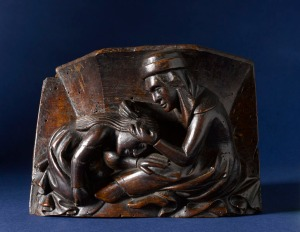 A misericord of a women picking nits [?] from the RAMM Hems Collection